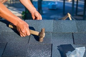 Worker Repairing Asphalt Roof Shingles