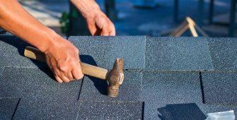 Worker Repairing Asphalt Roof Shingles