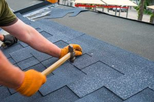 Man Replacing Roof Shingles