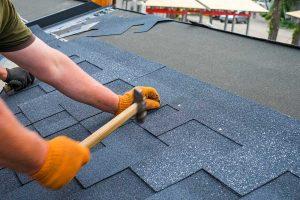 Man Replacing Roof Shingles